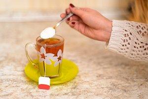 Woman puting sugar into tea cup