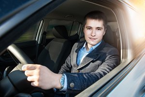 Young businessman driving a car