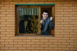 man showing keys from the window