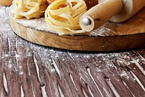 Uncooked pasta with flour on the table, selective focus