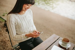 Woman sitting at cafe using mobile