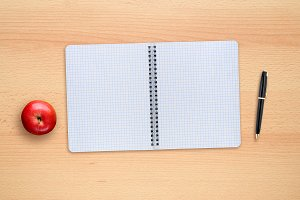School copybook, pen and apple