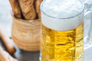 Glass of beer with breadsticks