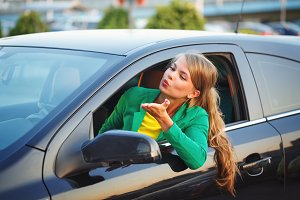 Girl sends air kiss of car