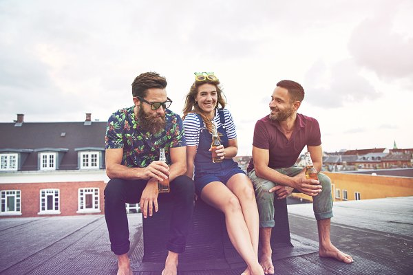 Two men and a woman drinking beer t…