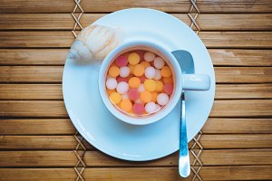 Top view of white coffee cup filled with colorful marmalade placed on a plate with tea spoon and seashell on wooden background