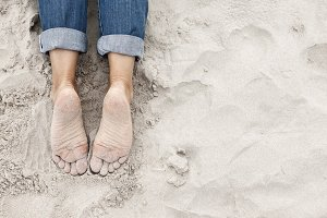 Sandy young woman feet on the beach
