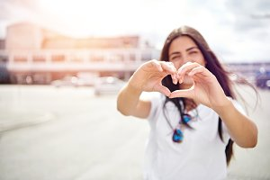 Pretty romantic young woman making a heart sign