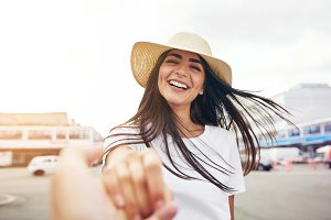 Smiling woman in white shirt stretches hand