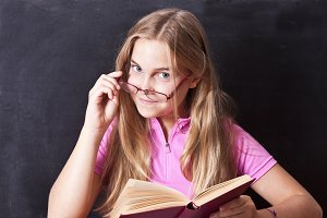 girl with spectacles and book at school with slate background