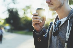 Young man holding coffee to go