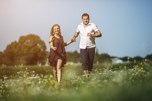 Couple running in field and have fun