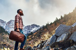 bearded traveler climbing mountain