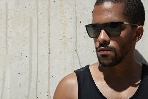 Headshot of attractive dark-skinned sportsman wearing stylish sunglasses and black sleeveless shirt, standing against gray concrete wall background with copy space for your text or advertisement