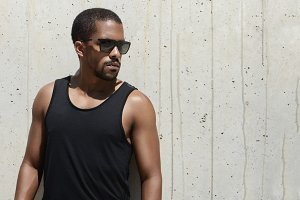 Handsome African runner with muscular athletic arms wearing stylish sunglasses and black sleeveless shirt, looking away while standing by concrete wall, waiting for friends to join him in his run