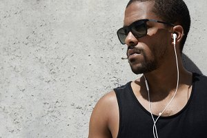 Profile portrait of black sportsman in black sleeveless shirt and hipster sunglasses having rest after his morning outdoor training, listening to music with headphones, standing at gray blank wall