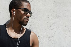 Close up of attractive African athlete with healthy tanned skin and confident look, wearing black sportswear and stylish sunglasses, resting outdoors, listening to his favorite music with earphones