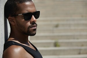 Headshot of dark-skinned athlete in black sunglasses, standing isolated againt steps of concrete stairs, relaxing after hard training exercises outdoors, preparing for serious sprint, looking away