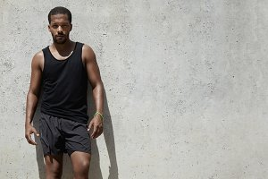 Attractive African athlete with muscular body in black sportswear standing against gray concrete wall background with copy space for your text or promotional content, relaxing after morning run