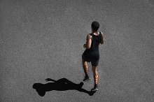People, sports and achievement. Top shot of athletic dark-skinned runner wearing black sportswear, jogging outdoors, casting shadow upon black pavement, training, preparing for serious marathon
