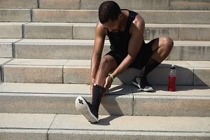 Dark-skinned athlete with muscular body wearing black outfit holding his injured leg with both hands, massaging his ankle, suffering from sprain after exercising outdoors, preparing for marathon