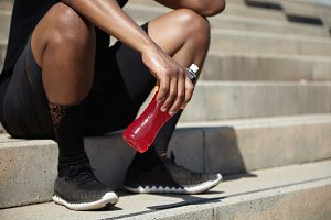 Young African jogger with muscular legs relaxing after evening run on embankment, sitting on sidewalks and enjoying fresh air on summer sunny day, holding plastic bottle of cold red drink or shake