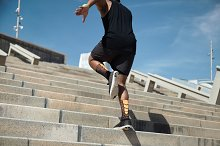 Back view of African American jogger dressed in black sportswear and sneakers, doing workout, jumping over concrete steps while exercising outdoors on summer sunny day, preparing for marathon