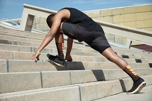 Young African jogger with fit athletic body wearing black running shoes and outfit doing stretching exercises, preparing for evening workout in park, leaning over his head, standing on concrete stair