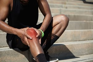 Close up shot of African athlete in black training socks and shoes clutching his injured knee, having twitch or sprain, touching it with his hands after hard training exercises in urban surroundings