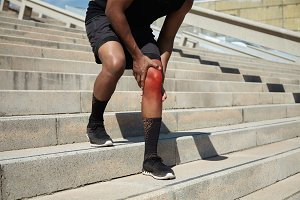 Sports and physical injury concept. Cropped shot of African jogger in black sportswear and running shoes having twitch or sprain in his red knee, standing outdoors, rubbing sore area with his hands
