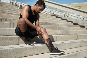 Black male jogger in black sportswear and athletic shoes sitting on stair outdoors clutching his aching knee, having spasm or twitch, massaging sore area after hard workout in city on sunny summer day