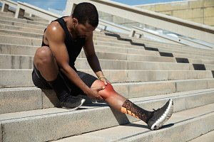 Portrait of dark-skinned athlete in black training outfit relaxing on concrete stairs after jogging exercises during his morning run, having pain in leg, touching his aching knee depicted in red color