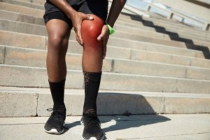 Physical injury concept. African jogger wearing black shorts and athletic shoes, standing on steps of concrete stair, having knee pain, preparing for marathon outdoors, massaging leg with his hands