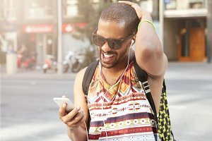 Attractive African American young man wearing sunglasses and backpack on his shoulders holding his head, screaming in indignation, understanding that he forgot his cell phone battery charger at home