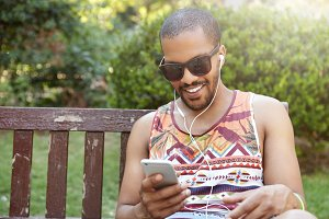 Cheerful young African American man wearing sunglasses, typing messages using mobile phone while having rest sitting on bench in city park, smiling, listening to his favourite music with earphones