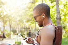 People and technology. Profile portrait of dark skinned guy drinking fresh green smoothie with straw, sitting in shade on summer evening, listening to music with earphones using mobile phone
