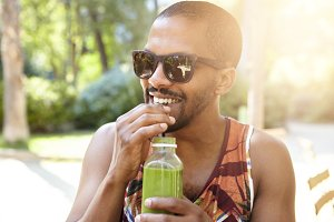 Young attractive African American hipster sipping fresh green smoothie, waiting for his friends at city park on hot summer day, hiding in the shadow of big trees, wearing fashionable sunglasses