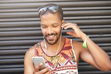 Street fashion style. Smiling good-looking attractive black hipster guy listening to contemporary music using his earphones and smart phone, looking at his mobile leaning against grey textured wall