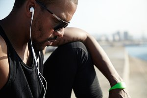 Close up shot of dark-skinned sports man wearing black sunglasses listening to audiobook with earphones while relaxing outdoors after workout, sitting alone at the sea on summer day, looking serious