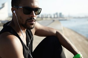 Handsome thoughtful young runner in sunglasses dressed in black sleeveless shirt, sitting on embankement, having rest, looking confident and serious at camera, listening to music on his smart phone