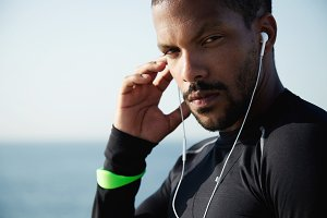 Life goals and achievement concept. Portrait of confident self-determined African athlete wearing black training outfit, listening to music during serious workout on sunny day on embankment at ocean