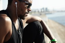 Profile portrait of young black runner in earphones relaxing after his morning workout in open air, listening to music, looking tired and exhausted, sitting on pavement, breathing fresh sea air
