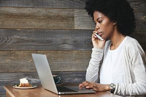 Technology and communication concept. Successful dark-skinned businesswoman with Afro hairstyle making phone calls with serious and confident look while working on laptop computer at hotel lobby