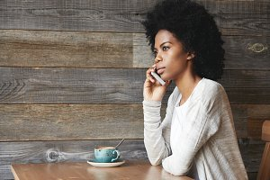 Successful African businesswoman wearing casual top talking on mobile phone to her partner, listening attentively, looking into distance with pensive expression, sitting at coffee shop during lunch