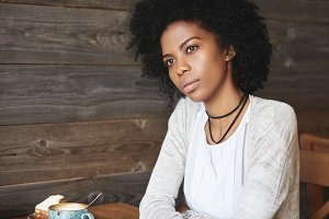 Attractive young black woman waiting for her friends at coffee shop, having cappuccino, with serious reflective look, against wooden wall background with copy space for your advertising content
