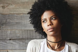 Highly-detailed portrait of good-looking dark-skinned young woman with perfect skin and stylish Afro haircut, looking away with pensive expression, dreaming of traveling or making future plans