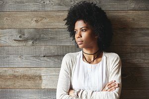 Attractive African American woman with Afro hairstyle standing with folded arms against wooden wall with copy space for your text or promotional content, looking away with serious expression