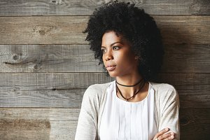 Beautiful young African woman, dressed casually, looking away at distance, posing with closed posture and thoughtful expression on her face, thinking about something while waiting for her friend