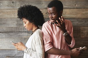 Portait of annoyed African man in glasses angry with his attractive girlfriend who is absorbed in surfing Internet and texting friends via social networks while standing back-to-back with her