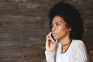 Isolated portrait of beautiful African woman with Afro hairstyle, talking on smart phone with serious and concerned expression, listening to some unexpected news, sitting alone at hotel lobby